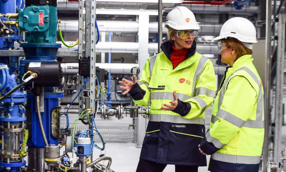 Emma Walmsley gesturing with both hands as she speaks to Nicola Sturgeon in a factory, with both women wearing hi-vis jackets, safety goggles and hard hats.
