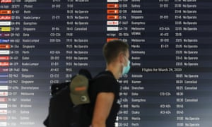 A traveller walks past a departures board showing cancelled flights