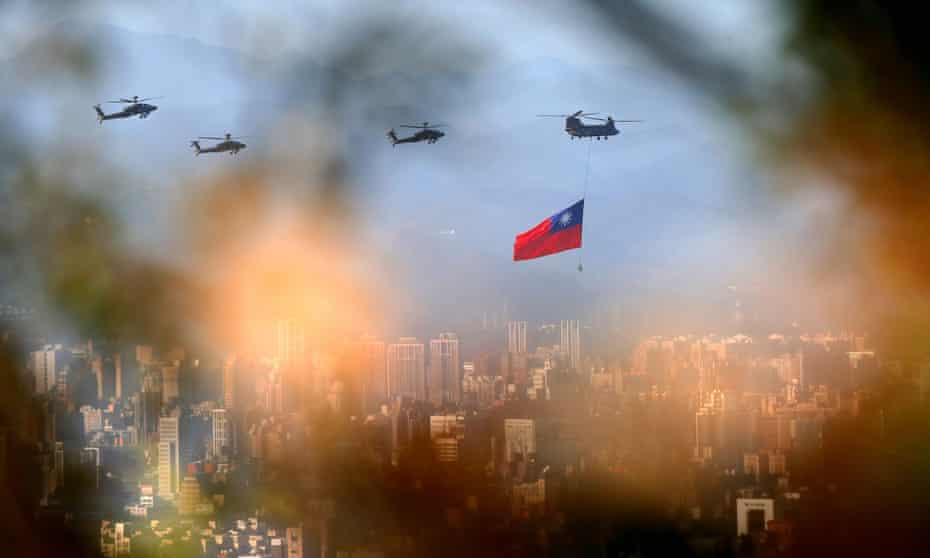 A military helicopter carrying a Taiwan flag flies over  Taipei.