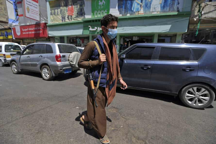 An armed Yemeni man, wearing a protective face mask, walks down a street in the capital Sana'a on 21 March, as the country prepares for an outbreak of coronavirus.