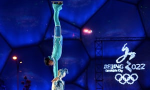 Chinese ice skaters in front of a 2022 bid campaign logo at the National Aquatics Centre in Beijing.