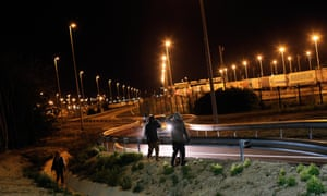 Migrants walk on a road outside the Eurotunnel area in Calais early Wednesday