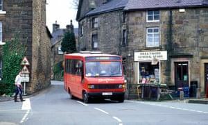 Local rural bus service passing village shop, Longnor, Peak District, Derbyshire