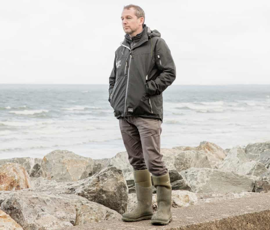 Gareth Evens, of Natural Resources Wales, standing on a sea wall at Fairbourne