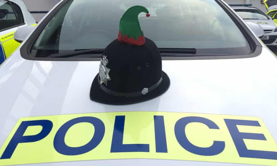 Police officer's helmet with elf hat appendage, on the hood of a police car.