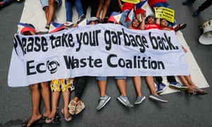 Demonstrators hold placards while lying down on the road during a protest at the Canadian Embassy in the Philippines