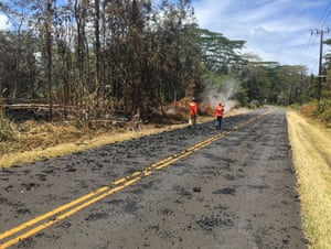 USGS scientists monitoring the eruption in Leilani Estates walk past spatter that was erupted from fissure 5-6 on Leilani Avenue