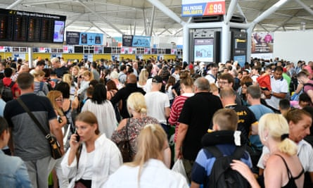 Passengers queue at London's Stansted airport
