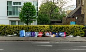 A row of estate agent boards lying on their sides next to a hedge