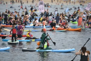 Surfers, paddleboarders and kayakers take part in an environmental protest in the water off Gyllyngvase beach in Falmouth.