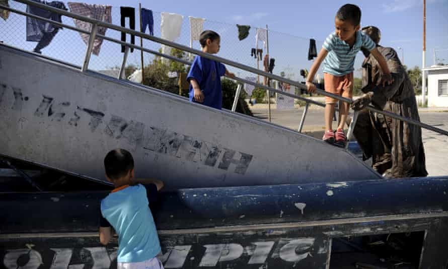 Children play on an old mobile staircase at the disused Ellinikon airport, now home to 2,000 refugees.
