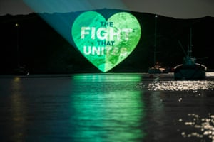 A green slogan is projected on to a cliffside in Lulworth Cove, England