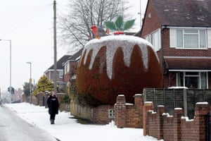 A passerby admires a fir tree outside the home of Roger and Valerie Holly in Yeovil, Somerset, which has been carefully pruned to resemble a giant Christmas pudding.
