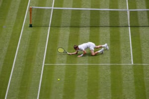 Alexander Bublik is down (and ultimately out) as he lies on the ground as he is passed by defending champion Andy Murray