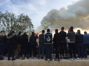 A group watch Notre Dame cathedral burn.
