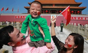Happy to be a big brother? A young family poses in front of Tiananmen Square in China. Last week, the country announced plans to repeal its one-child policy.
