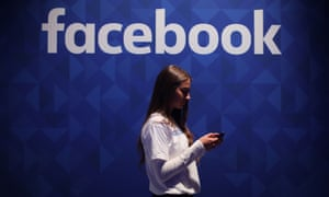 Woman on mobile under Facebook logo
