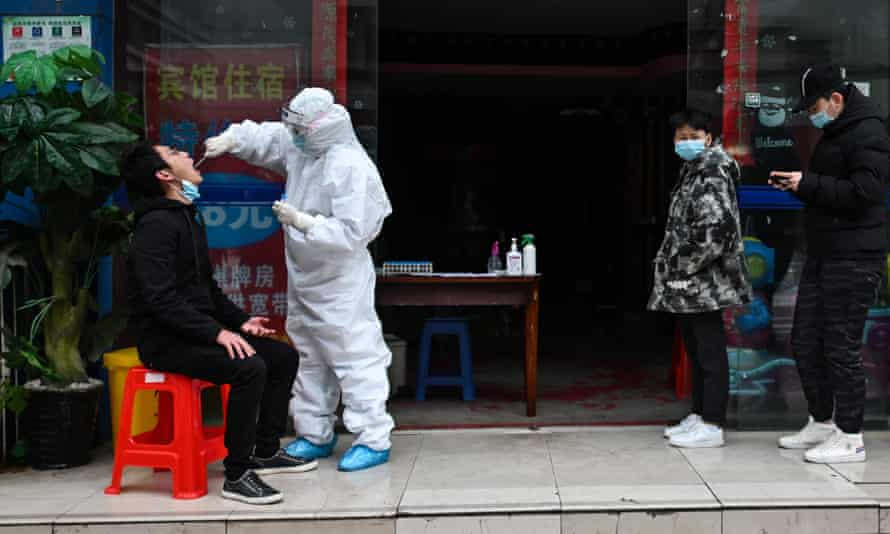 People wait in line to be tested for Covid-19 in Wuhan. The WHO has said it has no evidence that the virus came from a Chinese lab.