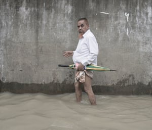 A man celebrating Eid wades through tidal flood in Chaktai, Chittagong, Bangladesh