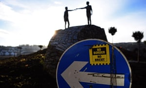 A protest sticker against a hard Irish border against the backdrop of the Hands Across the Divide sculpture by the sculptor Maurice Harron in Derry, Northern Ireland.