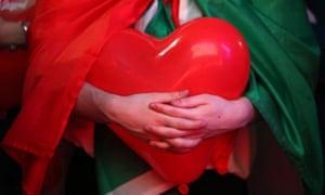 An Italy fan holds a balloon shaped like a heart