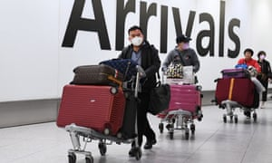 People wearing face masks arrive at Heathrow Airport