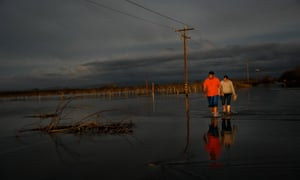 Melissa Martinez and her son, Fernando Martinez wade away from a flooded area near Oroville dam in northern California.