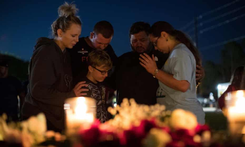 A group of people huddle and say a prayer after a vigil at Texas First Bank in Santa Fe.