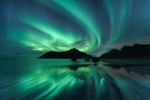 ReflectionBeate Behnke (Germany). The reflection in the wave ripples of Skagsanden beach mirrors the brilliant green whirls of the Aurora Borealis in the night sky overhead. To obtain the effect of the shiny surface, the photographer had to stand in the wave zone of the incoming flood, and only when the water receded very low did the opportunity to capture the beautiful scene occur