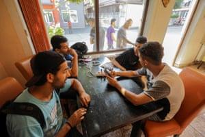 Migrants charge their phones at a Velika Kladusa restaurant