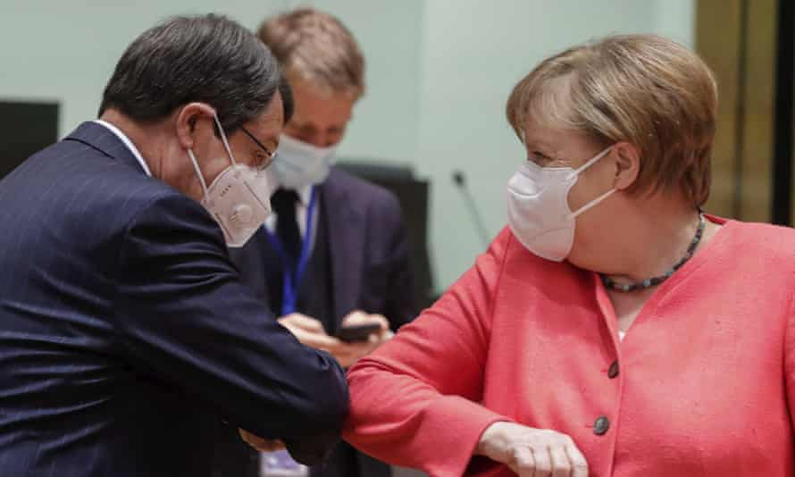 Angela Merkel greets the Cypriot president, Nicos Anastasiades, with an elbow bump at the EU summit in Brussels