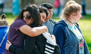 Santa Fe high school freshman Caitlyn Girouard, center, hugs her friend outside the Alamo gym after the Santa Fe shooting on 18 May.