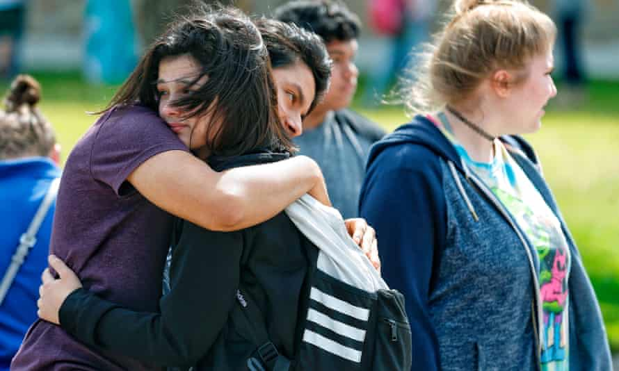 Santa Fe high school students hug each other outside the Alamo gym after the shooting on 18 May.