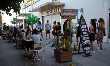 People sit at a bar near Barceloneta beach in Barcelona, Spain, after regional authorities and the city council announced restrictions to contain the spread of Covid-19
