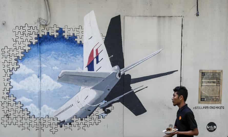 A waiter walks past a mural of flight MH370 outside Kuala Lumpur.