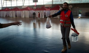 A French Red Cross volunteer hands out aid in a sports hall being used as a makeshift shelter.