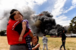 Locals watch as a helicopter drops water onto a blazing tyre fire in an industrial area in Melbourne in January.