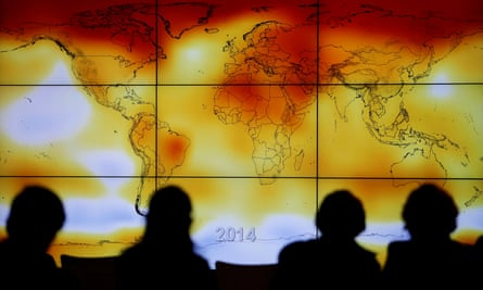 Participants at a 2015 UN climate conference look at a world map of rising global temperatures.