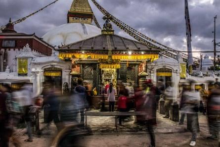 A woman stops to pray among other worshippers circumambulating the stupa at Boudhanath in Kathmandu, Nepal