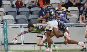 Curtis Scott fended off the Cowboys' Murray Taulagi to score as the Raiders won in Townsville