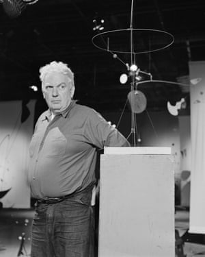 Alexander Calder with some of his mobiles