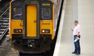 A man checks his phone on a station platform