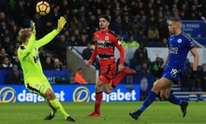 Leicester City's Islam Slimani (R) scores the team's second goal past Huddersfield Town's Danish goalkeeper Jonas Lossl (L).