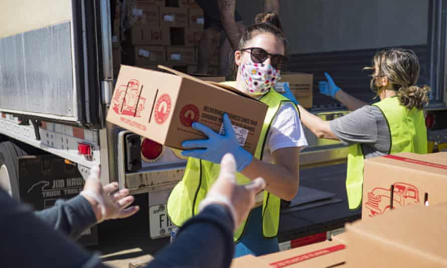 A volunteer, stacks boxes during a produce distribution in a mall parking lot in Des Moines, Iowa. Because of the Covid-19 pandemic, the unemployment rate in Iowa hit 10.2% in May, the highest ever recorded in Iowa