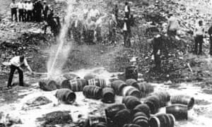 Beer barrels are destroyed by prohibition agents in an unknown location.
