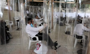 Ultra-Orthodox Jews pray in a separation nylon capsules at the Jewish Quarter, in Jerusalem's Old City, 25 October 2020.