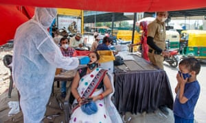 A health worker collects a swab sample from a woman at a testing site in India.