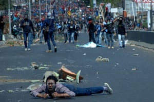 Makassar, IndonesiaA man lies on the road as protesters clash with police during university students' protest