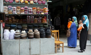 Uighur women in loose, full-length garments and headscarves associated with conservative Islam visit a market in the city of Aksu in western China's Xinjiang province.