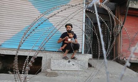 A Kashmiri man feeds his child near a police barricade in Srinagar, Kashmir